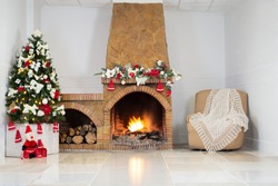 Christmas background,decorated christmas tree, bright lights, stone fireplace, christmas tree garland, armchair, knitted warm cape on glossy marble floor .Christmas interior decor