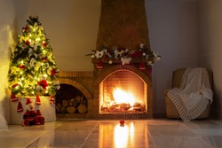 Christmas background,decorated christmas tree, bright lights, stone fireplace, christmas tree garland, armchair, knitted warm cape on glossy marble floor lights off.Christmas interior decor
