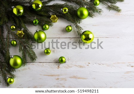 Christmas background decorated with green ornaments. New year greeting card with bauble hanging. Copy space.