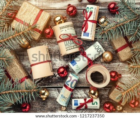 Christmas background, fir branches, gifts, baubles, money of different values. Top view.