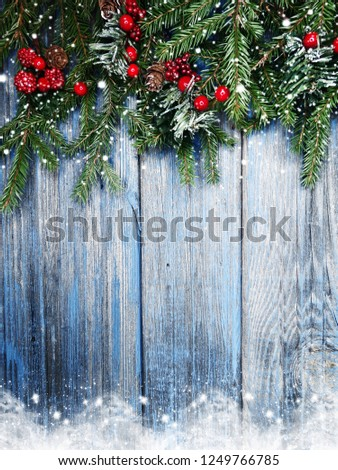 christmas background fir tree branch with cones and snow on wooden blue board #1249766785