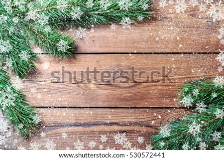 Christmas background for your design. Copy space. The branches of spruce on a wooden rustic background. Image decorated with snowflakes. #530572441