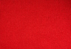 Christmas background from red knitted wool closeup
