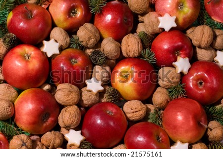 christmas background from the red apples, cookies and walnuts