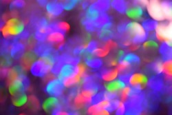 Christmas background, garland in blur. Glowing and festive rainbow light circles created in camera and bokeh lens. Christmas fairy lights are defocused giving a blurry effect.