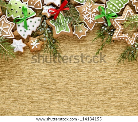 Christmas background. Ginger and Honey cookies with fir tree branches and bows on the gold wrapping paper background.