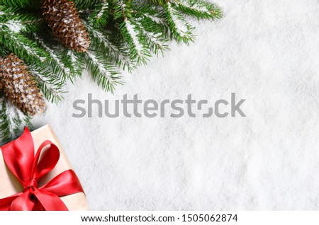 Christmas background, green pine branches, cones and gift box on snow background. Creative composition with border and copy space, top view. New Year's, holiday, christmas, decoration