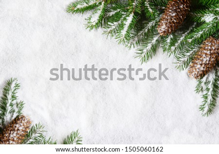 Christmas background, green pine branches, cones on snow background. Creative composition with border and copy space, top view. New Year's, holiday, christmas, decoration
