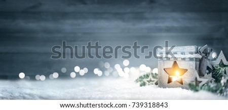 Christmas background in cool winter colors with a shining lantern, wood board, fir branches, ornaments and out of focus lights #739318843