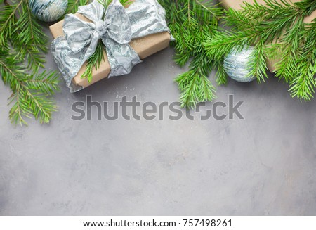 Christmas background in gray-blue colors with gifts wrapped in kraft paper, with ribbons, with glass Christmas-tree balls and xmas tree. Flat lay, top view #757498261