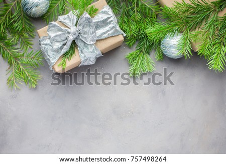 Christmas background in gray-blue colors with gifts wrapped in kraft paper, with ribbons, with glass Christmas-tree balls and xmas tree. Flat lay, top view - Shutterstock ID 757498264