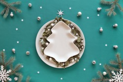 Christmas background in green and white. Xmas tree shape plate with copy-space on table covered with green mint textile. Fir tree twigs, snowflakes, paper star confetti. Holly leaves on round plate.