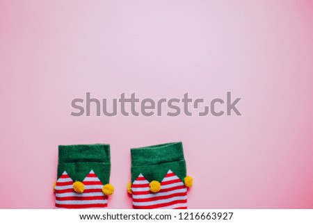 christmas background. minimalistic flat lay top view of elf socks. perfect for a festive merry xmas greeting card. enough room for copy space and text. #1216663927
