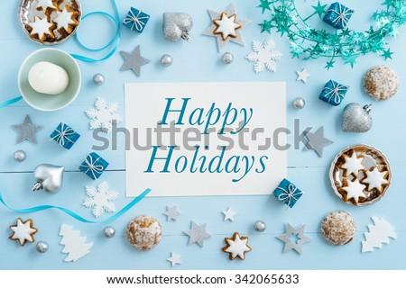 Christmas background, mockup, postcard or website header design with the words Happy Holidays on blue wooden table