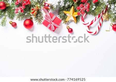 Christmas background. Red and gold christmas decorations with snow fir tree branch on white background isolated. Top view with copy space. #774169525