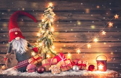 Christmas background. Santa Claus or dwarf holds a fir tree with Christmas lights surrounded by gift boxes and glowing lantern on rustic wooden