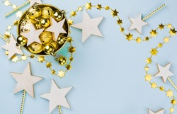 Christmas background,scattered gold decorations on table ,Wooden White Rustic Star,Copyspace, Blue backdrop, top view,flat lay