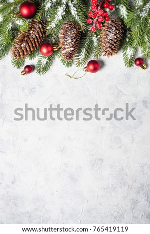 Christmas background. Snow Fir tree branch, pine cones, red balls and berries on gray stone table. Top view vertical. #765419119