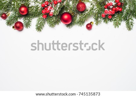 Christmas background. Snow Fir tree branch, red balls and berries on white background isolated. Top view with copy space. #745135873