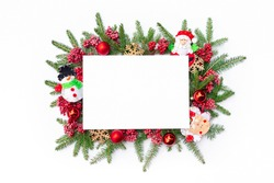 Christmas background with a frame of fir branches and Christmas tree decorations in the Scandinavian style. Christmas design template or mockup with white sheet of paper and  copy space.