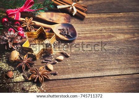 Christmas background with baking utensils, spices, anise stars, fir branches and  holiday decoration on dark rustic wooden table #745711372