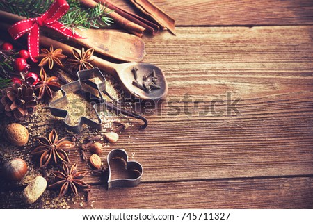 Christmas background with baking utensils, spices, anise stars, fir branches and holiday decoration on dark rustic wooden table #745711327