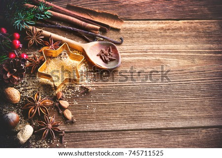 Christmas background with baking utensils, spices, anise stars, fir branches and holiday decoration on dark rustic wooden table #745711525