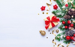 Christmas background with beautiful golden gift or present box, snowy fir branches, conifer cones, holiday decoration and red berry. Top view
