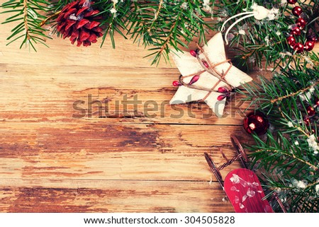 Christmas background with Christmas fir tree, star, pine cones and sleigh on the old wooden board in vintage style. Christmas concept with copy space for text. Retro style toned.