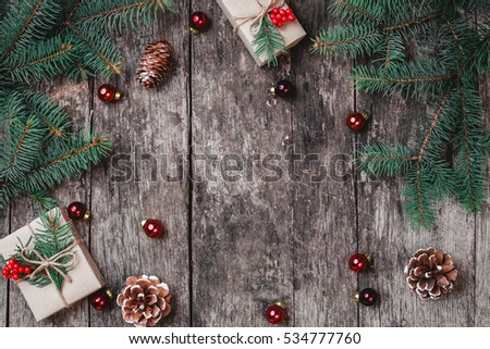 Christmas background with Christmas gift, pine cones, red decorations on wooden background with Fir branches. Xmas and Happy New Year composition. Flat lay, top view #534777760