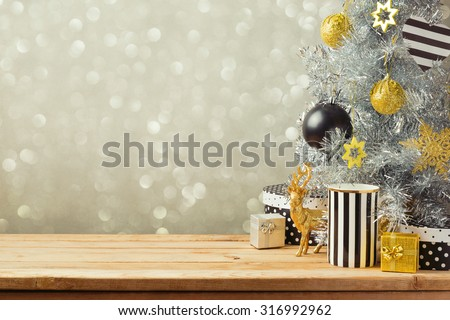 Christmas background with Christmas tree on wooden table. Black, golden and silver ornaments