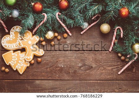 Photo of Christmas Background with Christmas Tree, Toys, Gingerbreads, Hazelnuts and Candy Canes on Brown Wooden Background, Free Space for Text, Toned Image