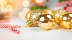 Christmas background with copy space, golden Christmas decorations and striped lollipops on a white table with bokeh and holiday and magic atmosphere, suitable for postcards and gift bags