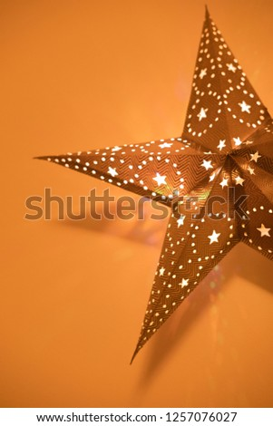 Christmas background with decorative star.  Decorative star with lamps on orange background. #1257076027