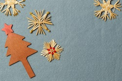 Christmas background with eco-friendly natural Christmas tree decorations made of wood and straw. On grey felt, with space