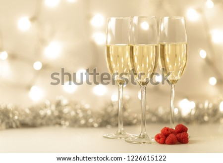 Christmas background with elegant flutes of champagne and a background bokeh of sparkling lights with decorations, fresh raspberries, and copy space for your holiday wishes #1226615122