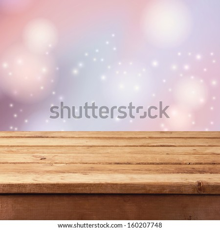 Christmas background with empty wooden table and winter bokeh background