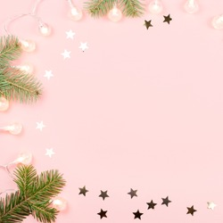 Christmas background with fir branches, Christmas lights and confetti on pink background. Copy space