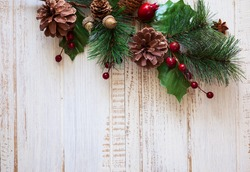 Christmas background with fir branches,pine cones and berries on the old wooden board
