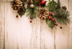 Christmas background with fir branches,pinecones and berries on the old wooden board
