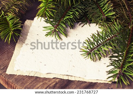 Christmas background with fir branches with blank paper on wooden planks, wooden table background, New year theme