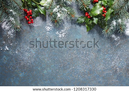 Christmas background with fir tree and holly berry on a blue stone background covered in snow with copy space. #1208317330