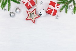 christmas background with fir tree branches, christmas balls and silver stars, red gift boxes and decorative wooden stars. fat lay