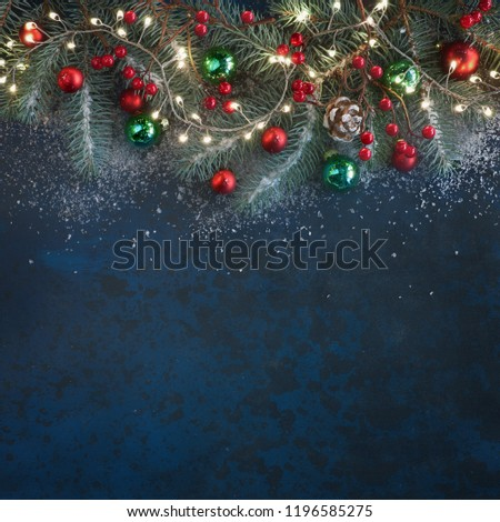 Christmas background with fir twigs, red berries, cones and Xmas lights on dark abstract background with plenty of text space #1196585275