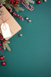 Christmas background with gift box and classic decorations. Fir branches, red balls, jingle bells on turquoise background. Gift box with tag.