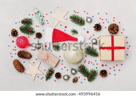 Christmas background with gift box, fir tree, conifer cone and holiday decorations on white desk top view. Flat lay styling.