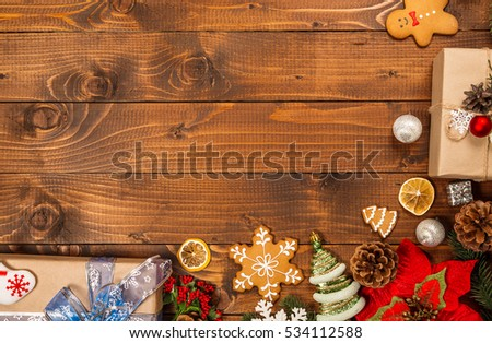 Christmas background with gifts, cookies, decor and fir tree branch on wooden table. Top view, with free space for you text. #534112588