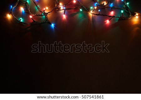 Christmas background with lights and free text space. Christmas lights border. Glowing colorful Christmas lights on black background. New Year. Christmas. Decor. Garland.