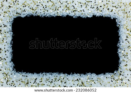 Christmas background with little golden stars on snow with black copy space