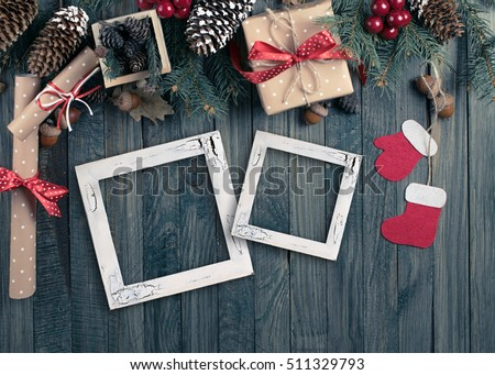 Christmas background with photo frame, spruce, gift box, Santa Claus boots and scroll in vintage style on wooden shabby boards. Top view.